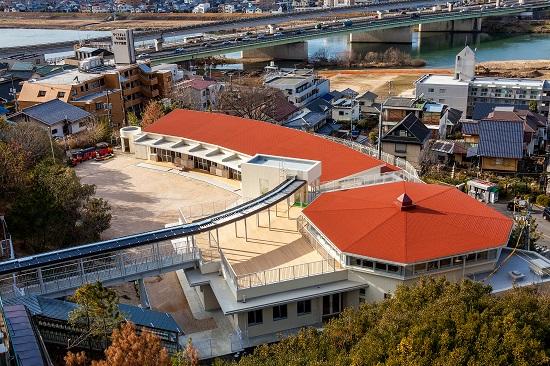 赤い勾配屋根は、奥に曲線を描く保育室、手前右に八角形の遊戯室。手前左の職員室は屋上に「ふれあい広場」を設けている